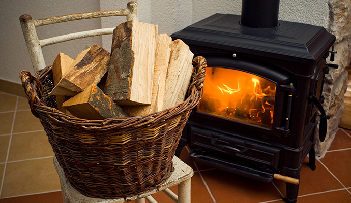 A wood stove with a bucket of wood next to it.