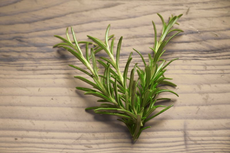 Flat lay of a stalk of rosemary on a wooden surface