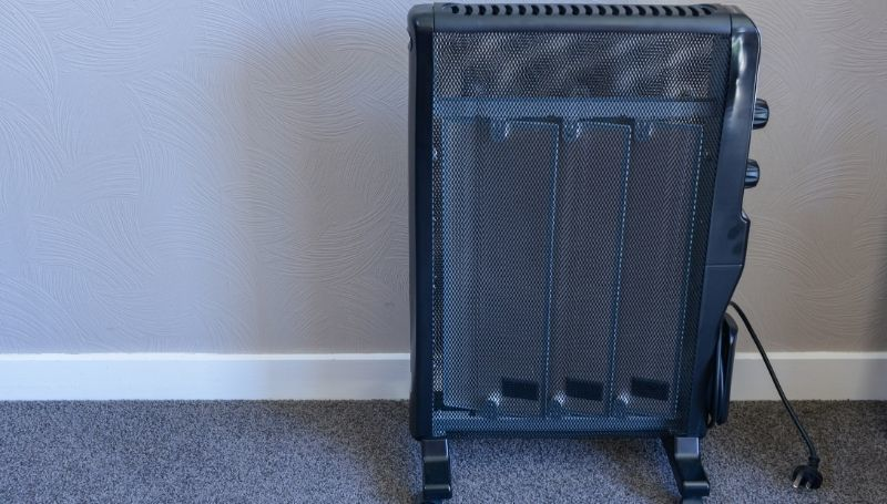 an unplugged all-black space heater on wheels