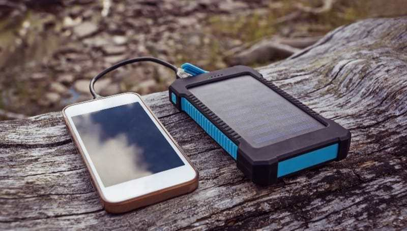 blue rugged solar power bank charging a phone outdoor
