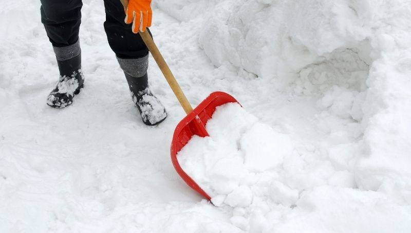 snow being shoveled by a person wearing gloves