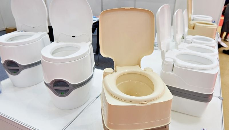 a display of composting toilets of different colors, sizes, and features
