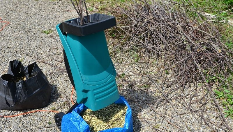 a blue wood chipper/shredder crushing dried twigs and branches