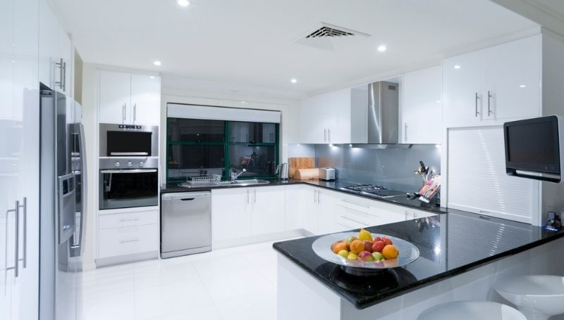 a modern white kitchen with black and chrome appliances and countertops