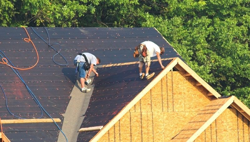 two people installing solar panels on the roof