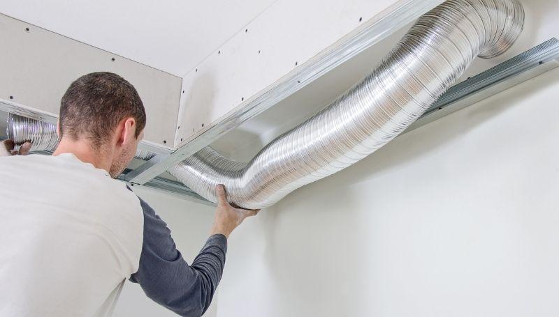 man setting up a flexible aluminum foil air ventilation duct