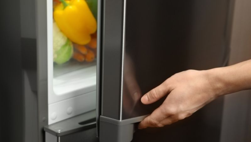 person opening an energy-efficient bottom-mounted freezer showing a few vegetables in the crisper