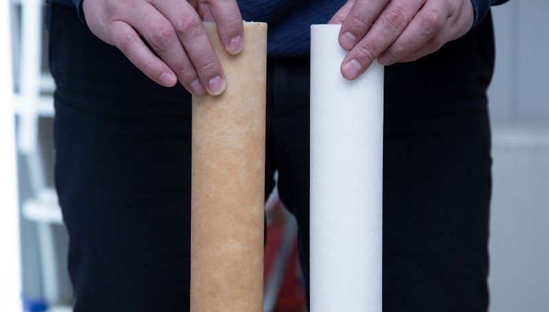 a person showing two gravity water filter cartridges: used (left) vs unused (right)