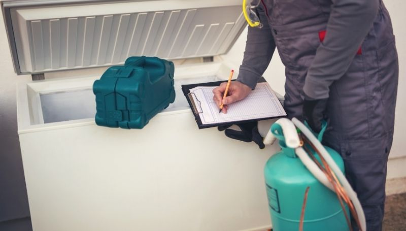 a man in grey jumpsuit installing a propane refrigerator | best off-grid refrigerator